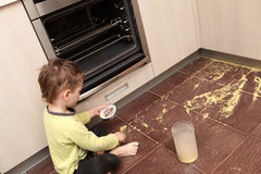 Child spilling cereal. In the kitchen at home Stock Photography