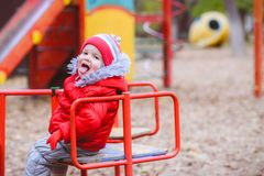 The child is spinning on a swing in the playground in the park. The kid is spinning on a swing in the playground in the park royalty free stock image
