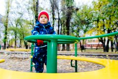The child is spinning on a swing in the playground in the park. The kid is spinning on a swing in the playground in the park stock image