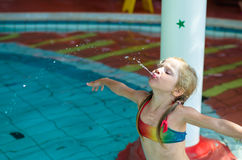 Child spitting water. Little blond girl in swimsuit and inflatable ring spitting water in the swimming pool Royalty Free Stock Photo