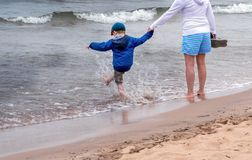 Child splashing in lake Michigan USA. A little boy happily kicks the water as he and his mom stroll along the shores of Lake Michigan USA stock image