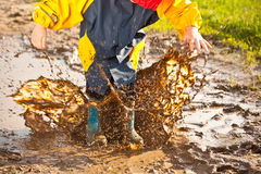 Child splashing in muddy puddle Stock Photo