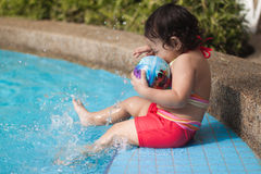 Child splashing water with feet by the pool stock images