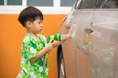 A child spraying water to wash a car Royalty Free Stock Photo