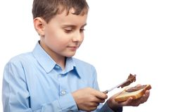 Child spreading peanut butter on bread Stock Photos
