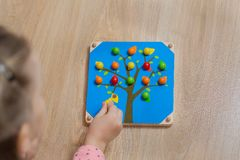The child spreads the color of the wooden balls. Game for children.  Stock Images
