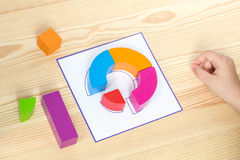Child spreads pattern according to pattern. Art; blocks; math; childhood; classroom; color; education; fun; game; kids; kindergarten; material; play; children Stock Photography
