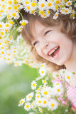 Child in spring. Happy child in wreath of flowers outdoors in spring park Royalty Free Stock Photography