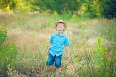 Child in spring field. Boy in a hat winks royalty free stock photography