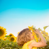 Child in spring field. Happy child having fun in spring field against blue sky background. Freedom concept Stock Photo
