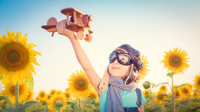 Child in spring field. Happy child playing with toy airplane against summer sky background. Travel and vacation concept. Retro toned Royalty Free Stock Images