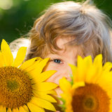 Child in spring. Happy child playing with sunflowers outdoors in spring park stock photo