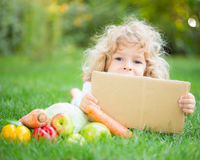Child in spring park. Happy child with fruits and vegetables holding paper blank against green spring background Royalty Free Stock Photography