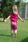 Child in Springtime. A happy beautiful blond caucasian healthy girl child in pink clothes running barefoot in the garden outdoors dancing and celebrating royalty free stock image
