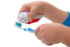 Child squeezes the toothpaste. Child's hand squeezes the toothpaste on the toothbrush royalty free stock photography