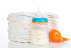 Child stack of diapers and baby feeding bottle with milk Royalty Free Stock Images