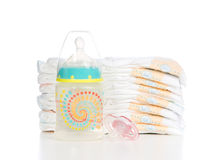 Child stack of diapers baby feeding bottle. New born child stack of diapers, nipple soother baby feeding bottle with water on a white background royalty free stock photos