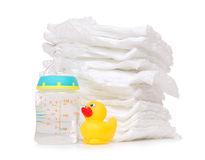Child stack of diapers bottle with water duck. New born child stack of diapers, nipple soother, baby feeding milk bottle with water and yellow duck on a white royalty free stock photos
