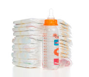 Child stack of diapers, nipple soother, baby feeding milk bottle. New born baby child stack of diapers, nipple soother, baby feeding milk bottle with water on a stock image