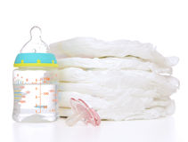 Child stack of diapers nipple soother feeding milk bottle with w. New born child stack of diapers, nipple soother, baby feeding milk bottle with water on a white royalty free stock photo