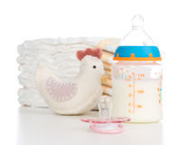 Child stack of diapers, nipple, toe and baby feeding bottle with. Child stack of diapers, nipple soother, toy and baby feeding bottle with milk on a white royalty free stock photos