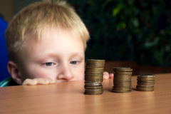 Child stacking coins. Happy child (boy, kid, teen) stacking coins on the table. Children and money concept Royalty Free Stock Photography