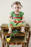 Child on stacking tables. A one year old girl sitting on decorative stacking tables with a yellow rose Royalty Free Stock Photos