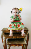Child on stacking tables. A one year old girl sitting on decorative stacking tables holding a yellow rose Royalty Free Stock Photo