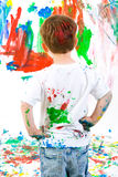 Child standing back and admiring his painting Stock Photos