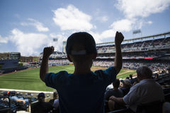 Child standing and cheering at a baseball game. An excited young baseball fan standing and cheering after an exciting play during a baseball game. Silhouette of Royalty Free Stock Images