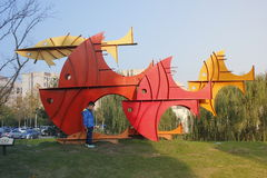 Child standing before the city sculpture which being colorful swimming fish Stock Photography