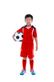 Child standing with closed eyes for concentrate before the compe. Full length of young asian soccer player in red uniform holding his soccer ball. Child standing Royalty Free Stock Image