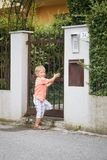 The child is standing at the entrance of a private house in the summer. royalty free stock photography