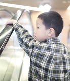 Child  standing on moving escalator Stock Images