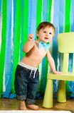 Child is standing near chair Stock Photo