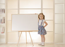 Child standing next to blank clipboard. Happy smiling beautiful little girl showing blank area for sign or copy space Royalty Free Stock Image