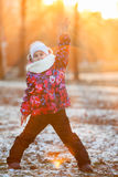 Child standing in the rays of the setting sun with raised hand, winter. Child standing in the rays of the setting sun with a raised hand, winter Royalty Free Stock Photo
