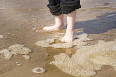 Child standing on the sand in shallow water. Child`s feet in the sand in the water near the sea Royalty Free Stock Photography