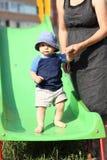 Child standing on slide Stock Photo