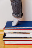Child standing on a stack of books Stock Photo