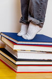 Child standing on a stack of books Stock Photos