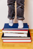 Child standing on a stack of books Royalty Free Stock Photos