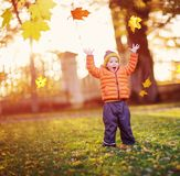 Child standing with umbrella in beautiful autumnal day stock photo