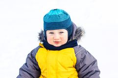 The child is standing in the winter snow over natural background stock photo