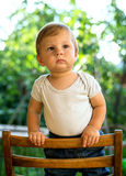 Child standing on a wooden chair Royalty Free Stock Image