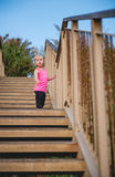 Child standing on wooden steps at beach looking down Stock Photos