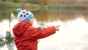 A child stands on the bank of the pond and throwing stones. Walks in the fresh air. A child stands on the bank of the pond and throwing stones stock footage