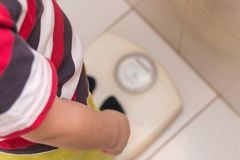 The child stands on the floor scales in a striped T-shirt, the view from the top. Health stock photo