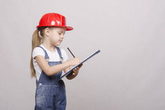 Child stands helmet and writes in the folder Stock Image