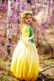 A child stands among the ledum and birch in green yellow dress, smiling and fly hair royalty free stock photography